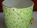 Zielona doniczka z metalową rączką